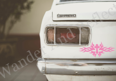 Pink vinyl decal of a cross set on tribal flames.