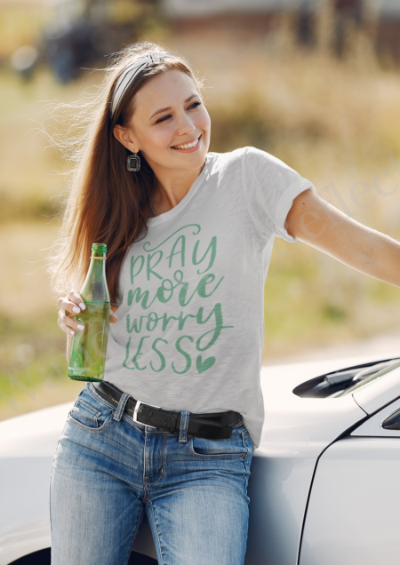 """Lowanda leans against the hood of a car drinking sparkling water while showing off her """"Pray more and worry less"""" custom shirt from Wander and Reflect."""